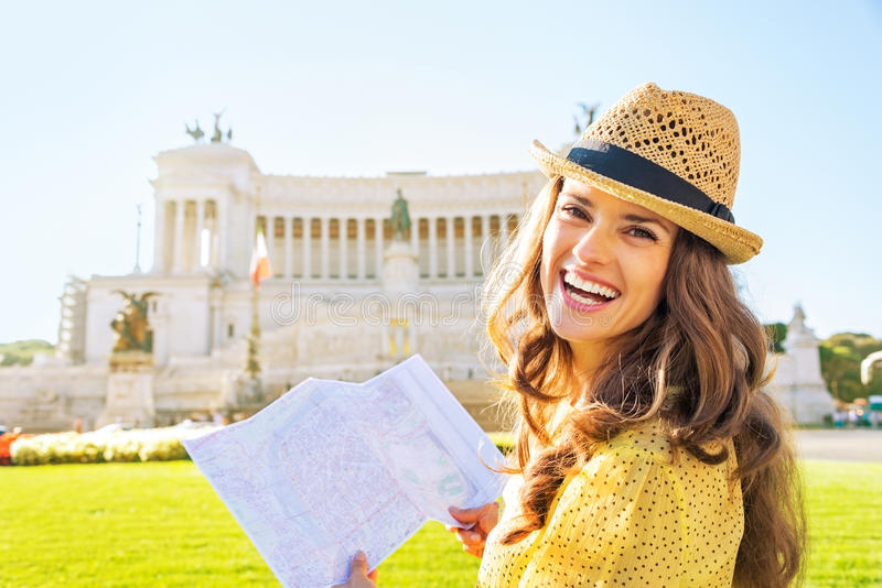 Woman with map examining attractions in rome. Portrait of happy young woman with map examining attractions on piazza venezia in rome, italy stock photography