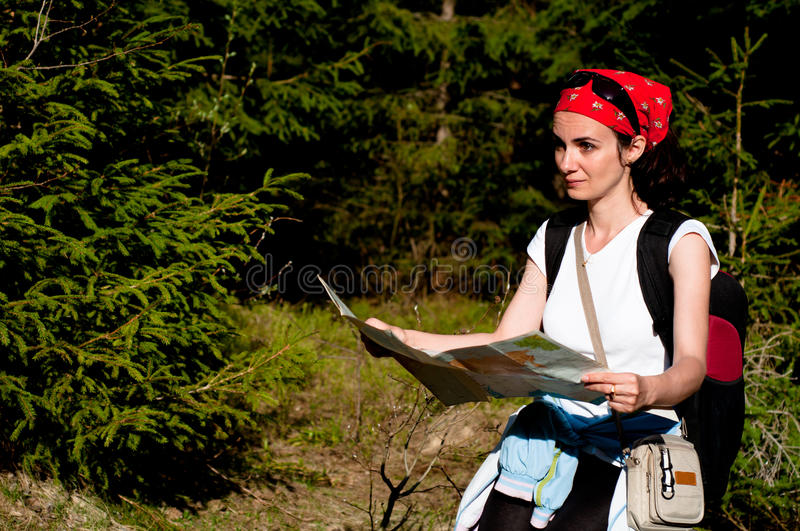 Woman with a map in forest. Woman orientating with a map in forest