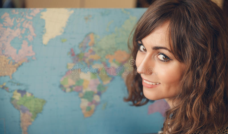 Woman with Map Looking over Shoulder at Camera. Woman with World Map in Background Looking over Shoulder at Camera as if Planning a Trip royalty free stock photos