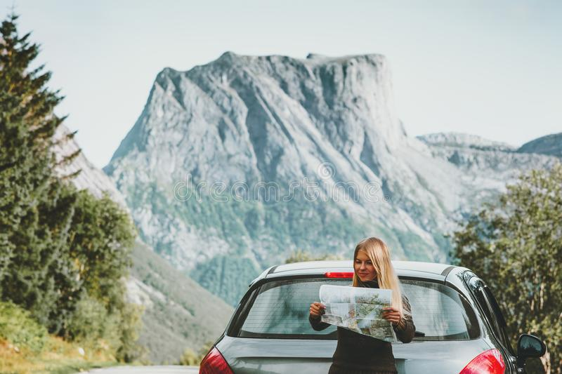 Woman with map on road trip planning journey route in Norway Travel Lifestyle concept adventure vacations outdoor mountains. On background stock photography