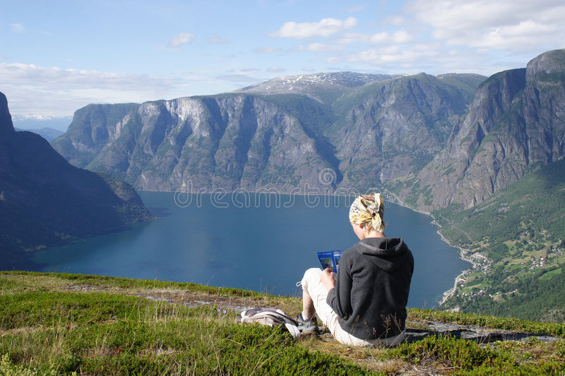 Woman with map sitting on the top of the mountain stock photography
