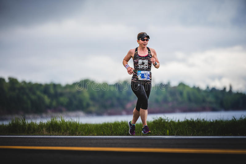 Woman Marathoner at about 7km of distance. CARLETON, CANADA - June 4, 2017. During the 5th Marathon of Carleton in Quebec, Canada. Woman Marathoner at about 7km stock image