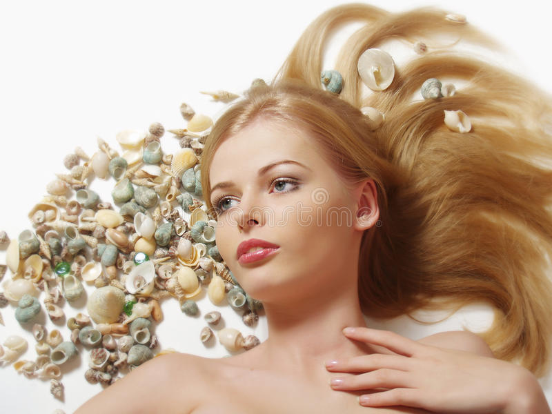 Woman with marine cockleshell in hair. Beautiful young blonde woman with marine cockleshell in her hair stock photo