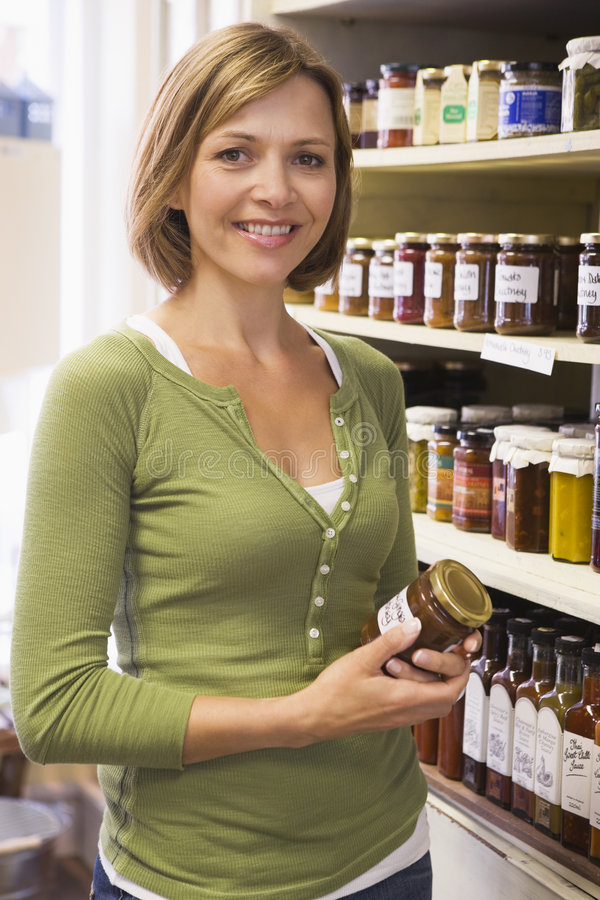 Download Woman In Market Looking At Preserves Smiling Stock Image - Image: 5940381