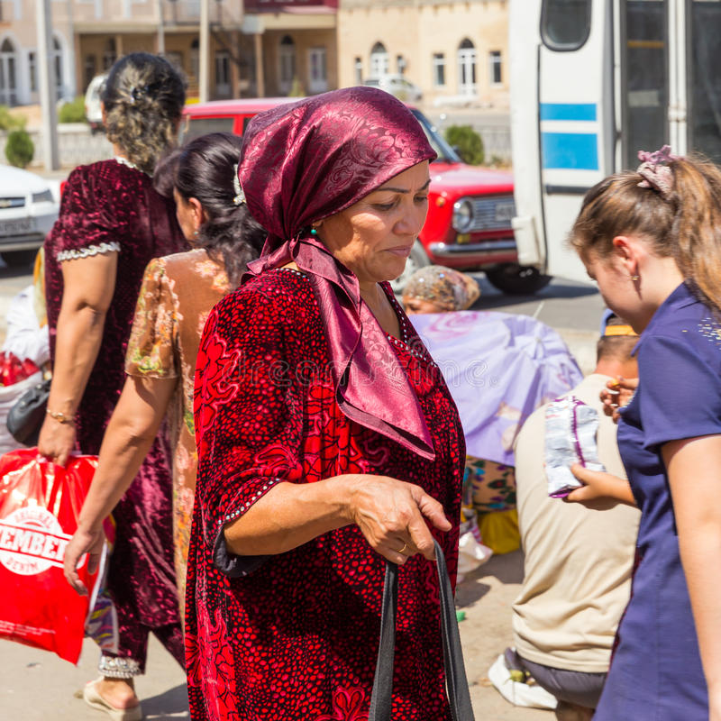 Woman at market in Samarkand, Uzbekistan. SAMARKAND, UZBEKISTAN - AUGUST 29, 2016: a woman goes shopping at the fruit and vegetable market in Samarkand stock image