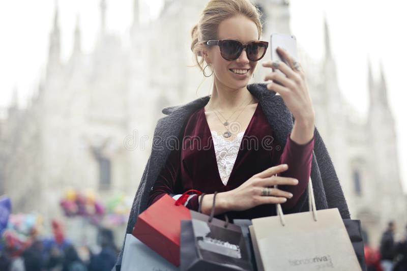 Woman in Maroon Long-sleeved Top Holding Smartphone With Shopping Bags at Daytime royalty free stock photography