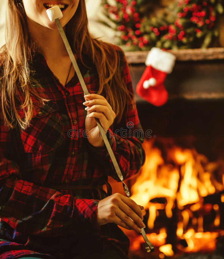 Woman with marshmallow by the fireplace. Young woman smiling and. Eating roasted marshmallow by the warm fireplace decorated for Christmas. Relaxed holiday stock photos