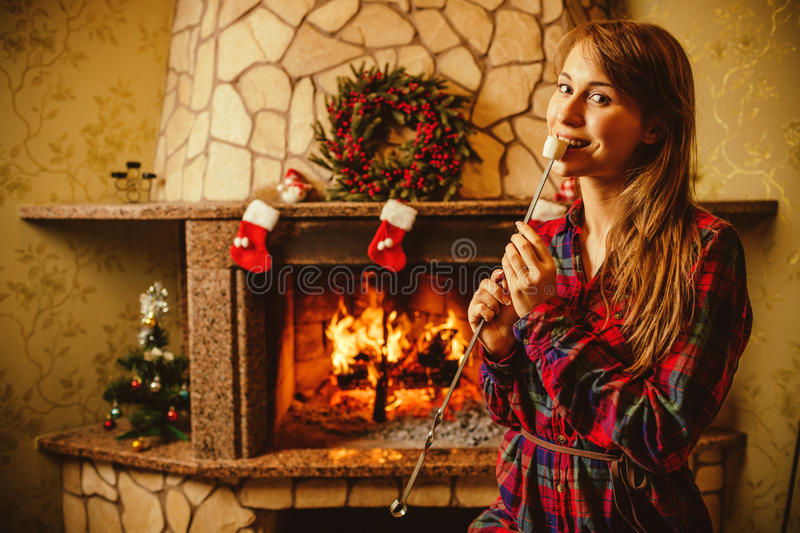 Woman with marshmallow by the fireplace. Young woman smiling and. Eating roasted marshmallow by the warm fireplace decorated for Christmas. Relaxed holiday royalty free stock images