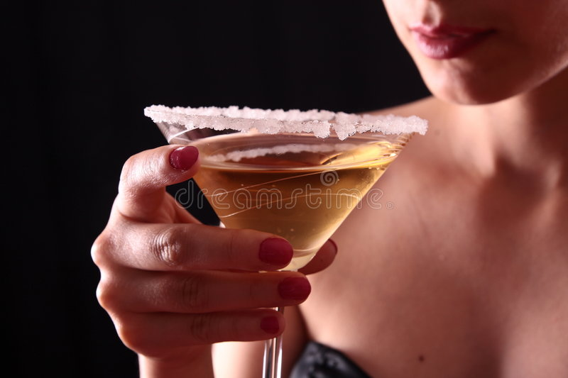 Woman and martini glass. Beautiful young woman holding a martini glass royalty free stock images