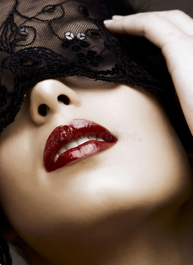 Woman in mask. Beautiful woman with red lips and lace mask over her eyes royalty free stock image
