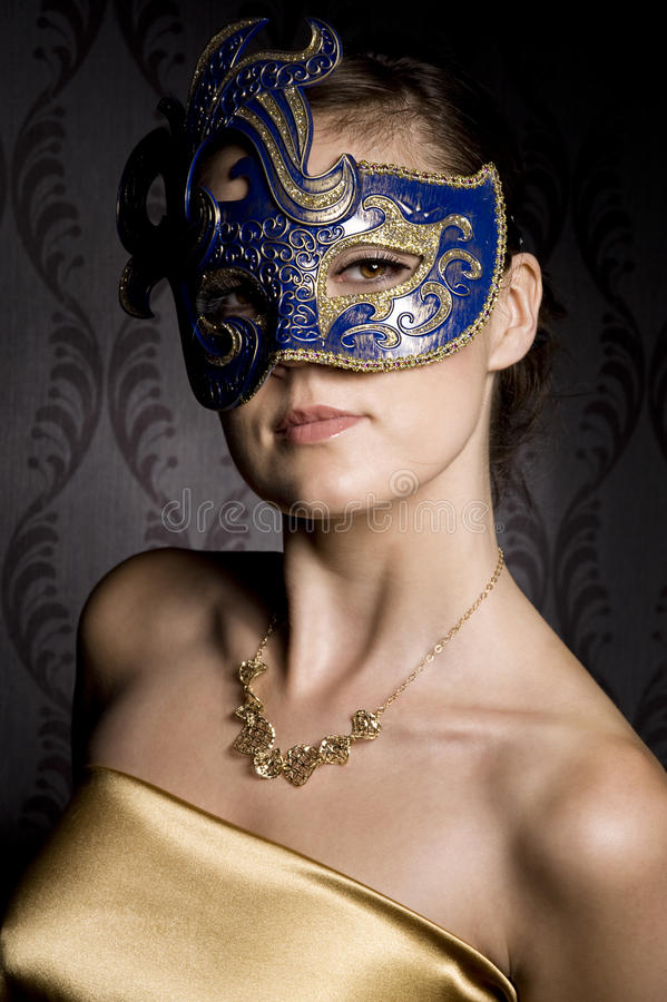 Woman in mask. Portrait of woman in mask over wallpaper background royalty free stock image