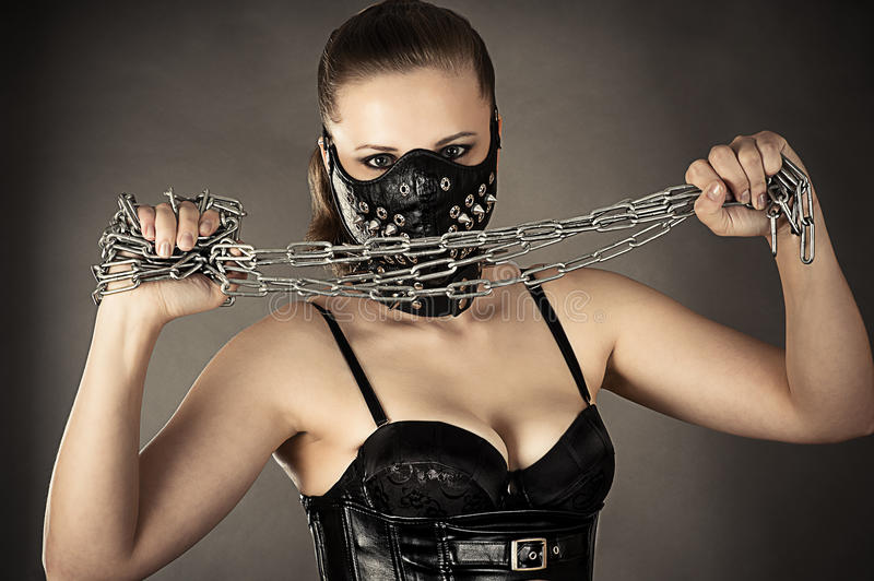 Woman in a mask with a chain in hands. Isolated on gray background royalty free stock photos