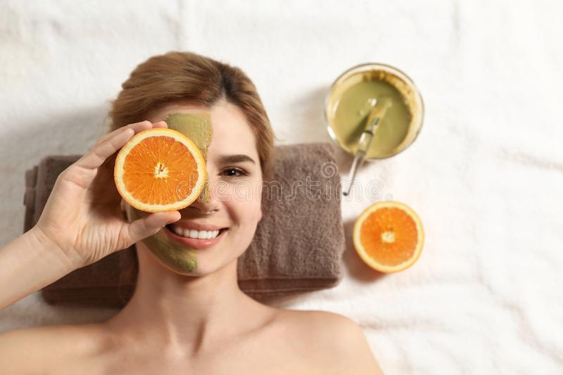 Woman with mask on face and cut orange relaxing in spa salon, top view. Space for text royalty free stock image