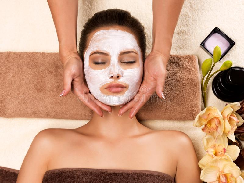Woman with mask on her face having head massage. Beautiful woman with mask on her face having head massage in the spa salon royalty free stock photo