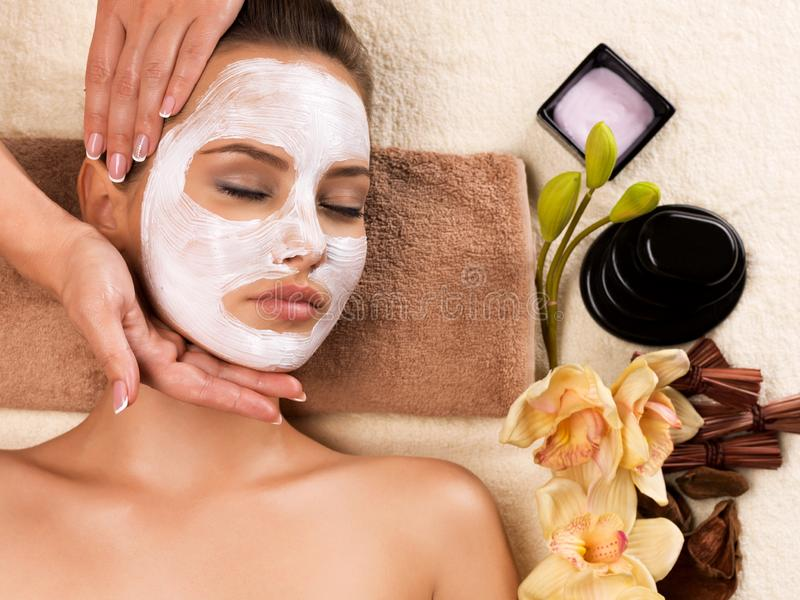 Woman with mask on her face having head massage. Beautiful woman with mask on her face having head massage in the spa salon stock image