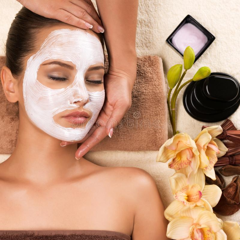 Woman with mask on her face having head massage. Beautiful woman with mask on her face having head massage in the spa salon stock photos