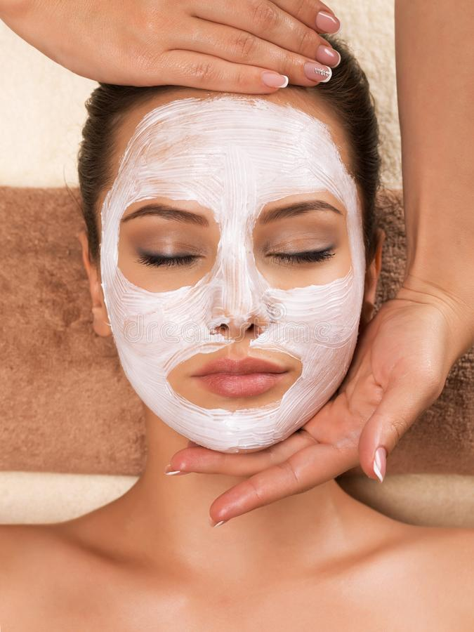 Woman with mask on her face having head massage. Beautiful woman with mask on her face having head massage in the spa salon stock images