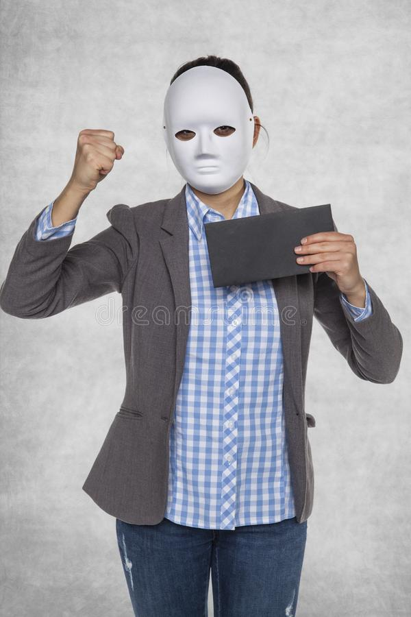 Woman in a mask holds an envelope in her hand. Isolated on background stock photography