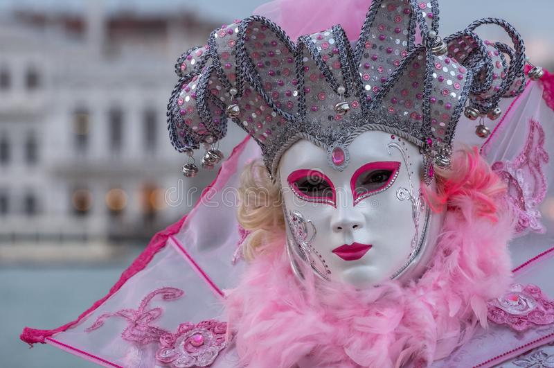 Woman in mask and ornate pink jester`s costume at Venice Carnival Carnivale di Venezia stock image