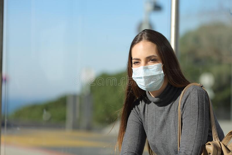 Woman with a mask preventing contagion waiting in a bus stop royalty free stock image
