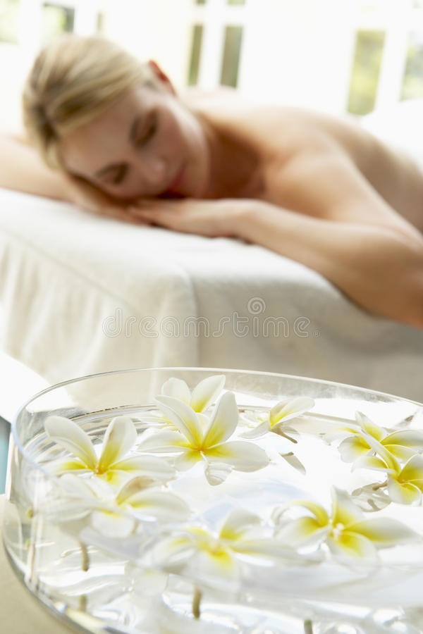 Woman On Massage Table With Flowers In Foreground. Relaxing royalty free stock photography