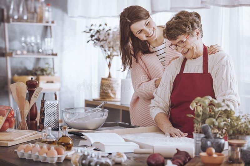 Woman massaging grandmother`s shoulder stock photo