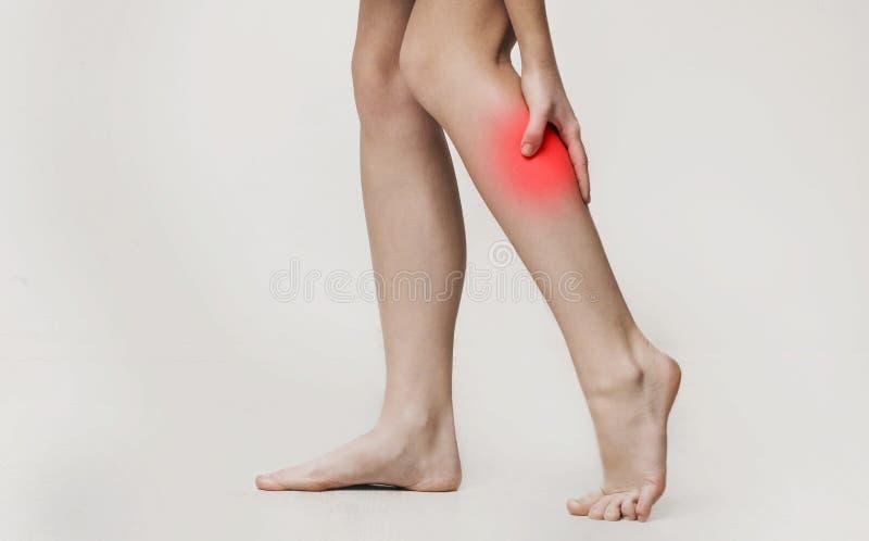 Woman massaging her painful leg calf, close up royalty free stock photo