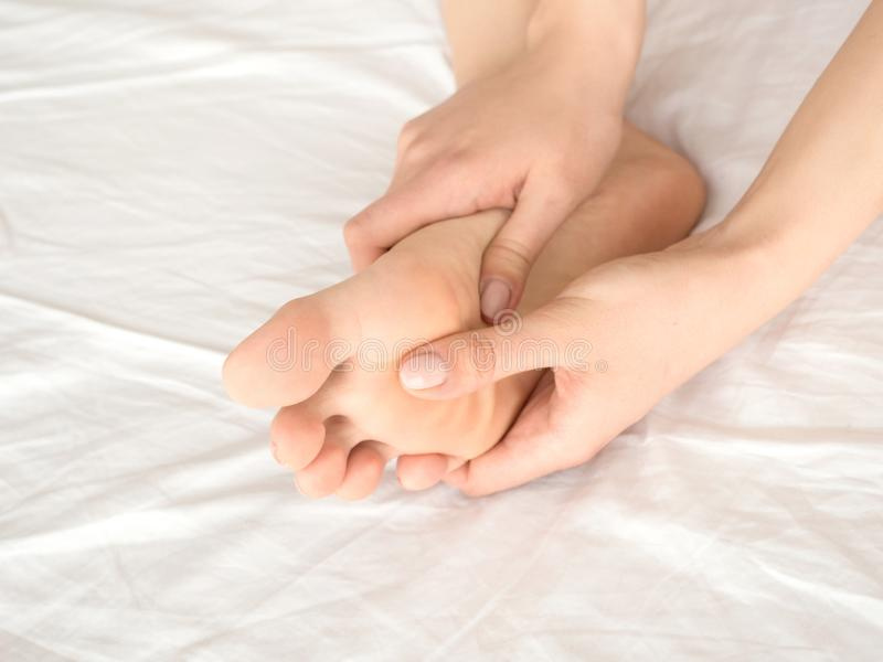 Woman massaging her tired feet on the bed. close up view. royalty free stock photo