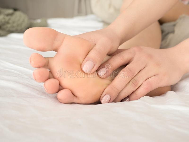 Woman massaging her tired feet on the bed. close up view. royalty free stock images