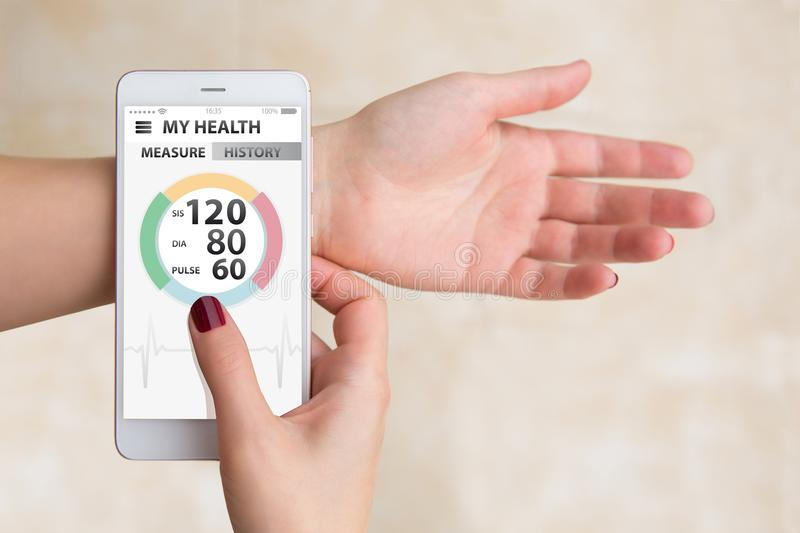 Woman measures blood pressure and pulse by mobile phone stock images