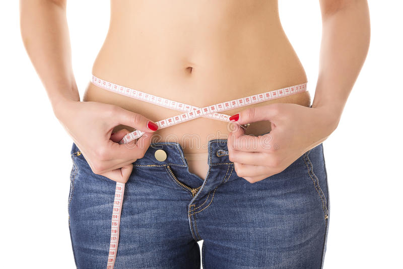 Woman measures the waist in jeans. royalty free stock images