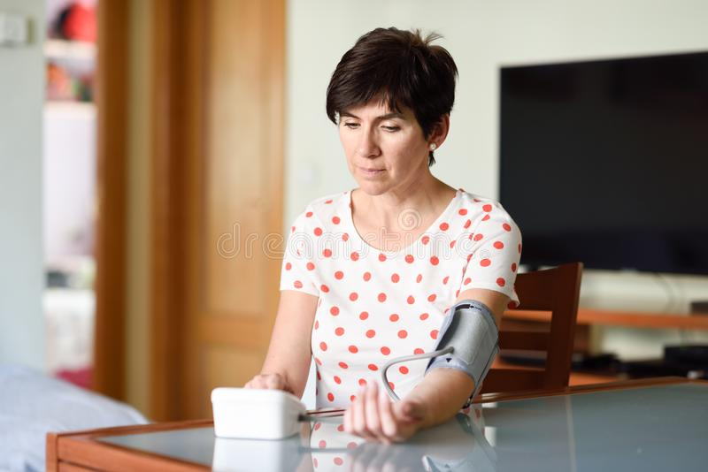 Woman measuring her own blood pressure at home. Middle-aged woman measuring her own blood pressure with an electronic blood pressure measurement device at home stock photography