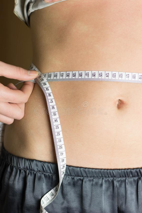 Woman measuring her waist. royalty free stock image