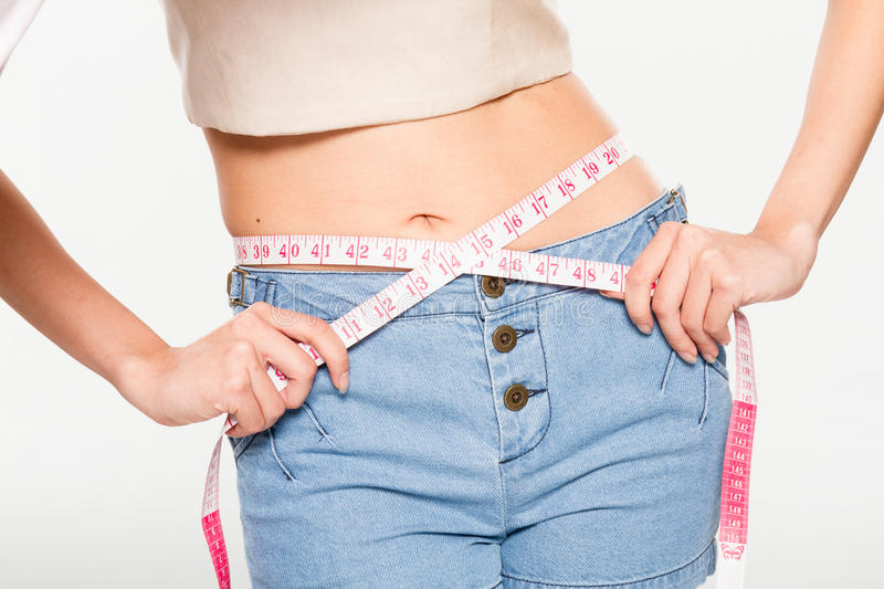 Woman measuring her waistline. On isolated background stock images