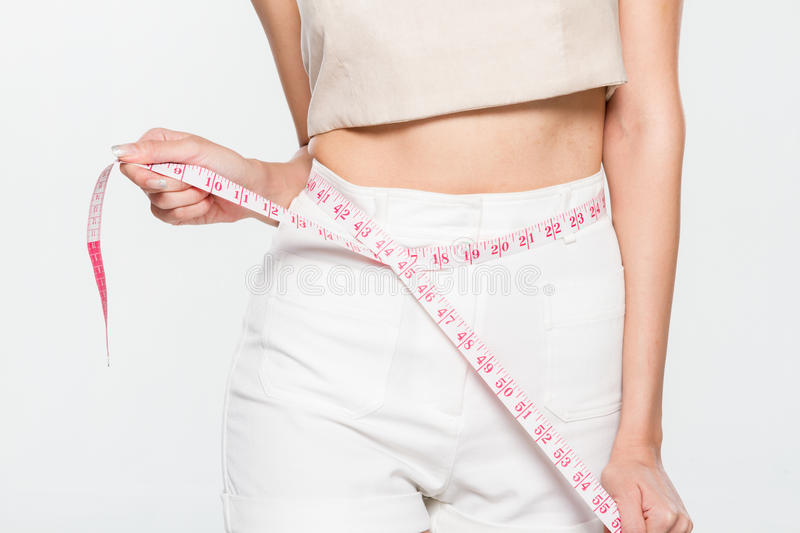 Woman measuring her waistline. On isolated background stock photo