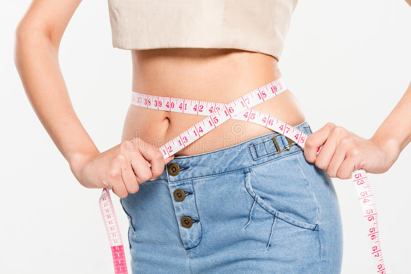 Woman measuring her waistline. On isolated background stock photos