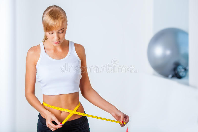 Woman measuring her waistline. Young beautiful woman measuring her waistline royalty free stock images