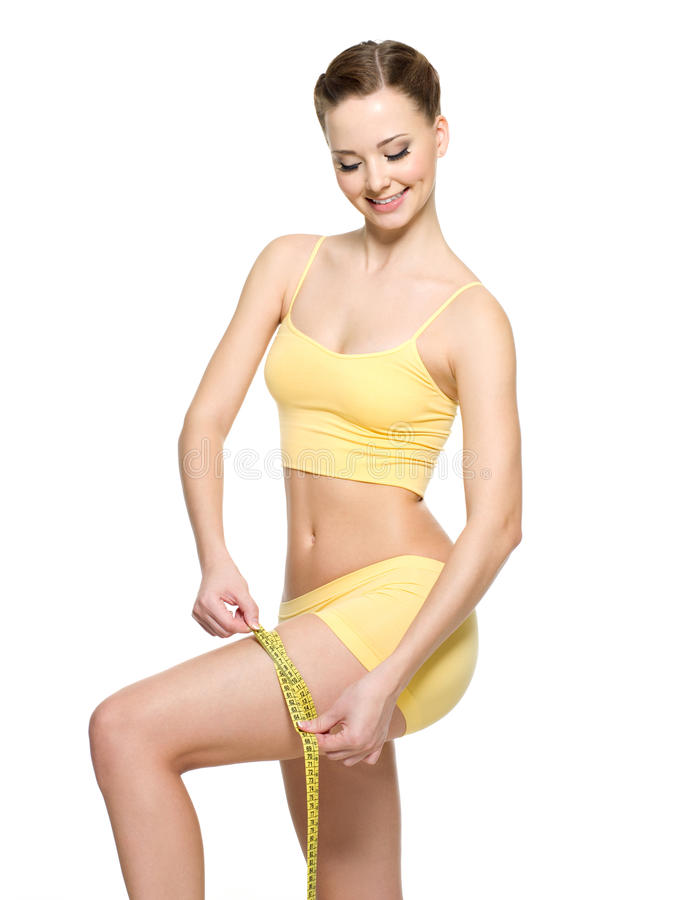 Woman measuring hip by tape after fitness stock images