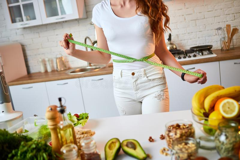 Woman measuring perfect shape of beautiful waist with green tape centimeter. Healthy Lifestyle and Eating. Health, Beauty, Diet royalty free stock photography