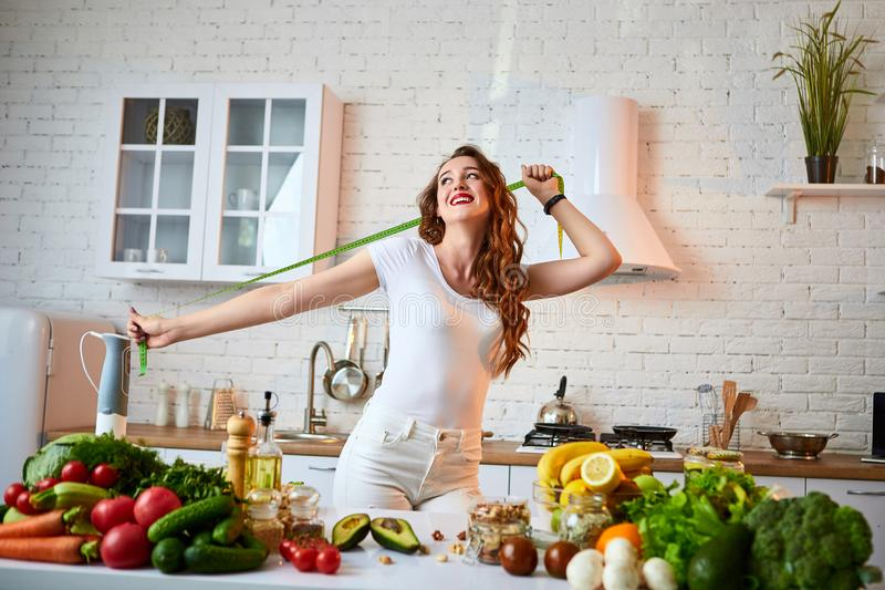 Woman measuring perfect shape of beautiful waist with green tape centimeter. Healthy Lifestyle and Eating. Health, Beauty, Diet. Woman measuring perfect shape of royalty free stock photo