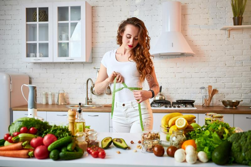 Woman measuring perfect shape of beautiful waist with green tape centimeter. Healthy Lifestyle and Eating. Health, Beauty, Diet. Woman measuring perfect shape of stock image