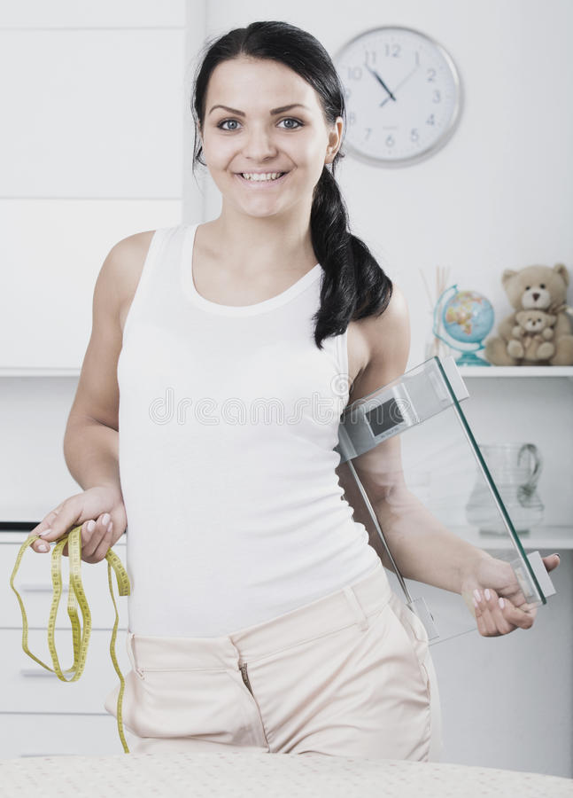 Woman with measuring tape and scales. Woman standing in room and holding measuring tape and scales royalty free stock photography