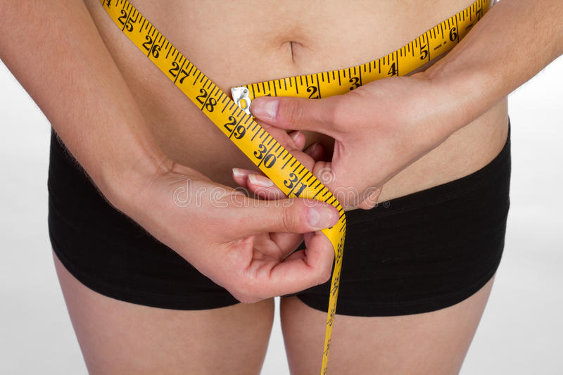Woman Measuring Waist. Weight loss woman measuring waist royalty free stock photos