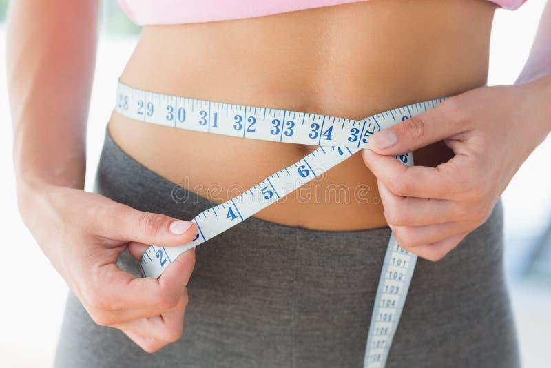 Woman measuring waist in fitness studio royalty free stock photos
