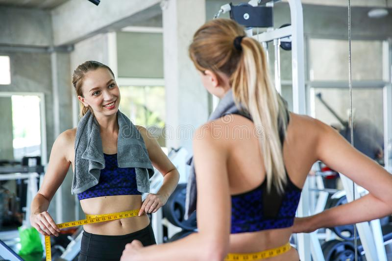 Woman measuring waist in gym. Slim woman measuring her thin waist with a tape measure. smiling people with measure tape in the stock photos