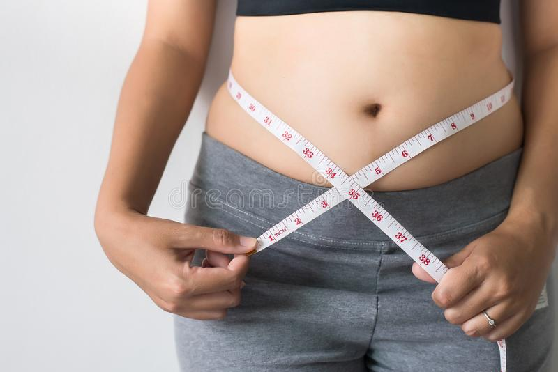 Woman measuring waist with measuring tape,Excess belly fat and overweight fatty bellys stock photos