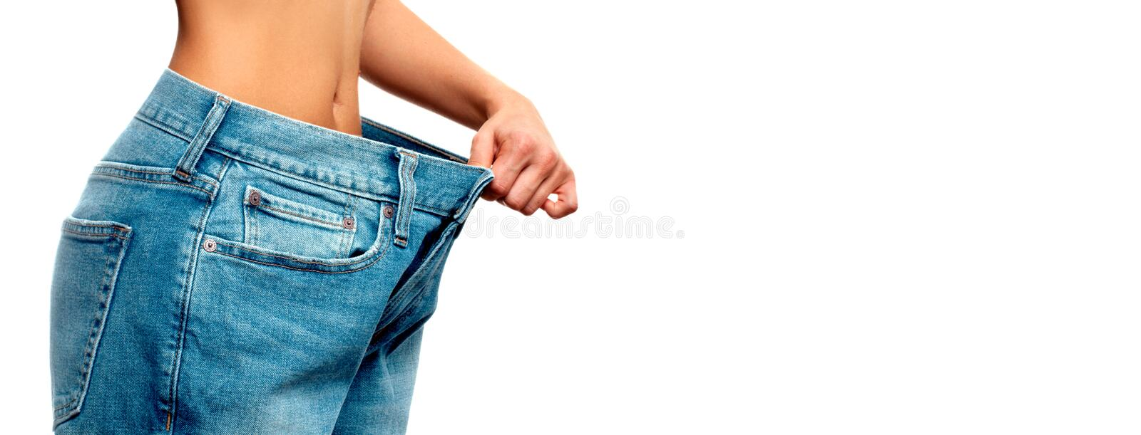 Woman is measuring waist after weight loss,. Diet concept. Woman is measuring waist after weight loss, diet concept. Woman in oversize jeans royalty free stock photo