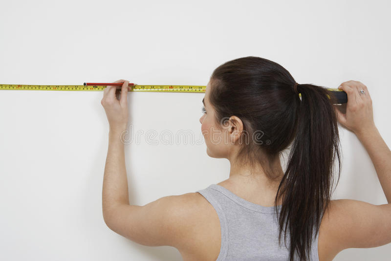 Woman Measuring Wall stock photography