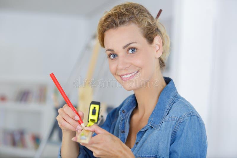 Woman measuring wood at home royalty free stock photos
