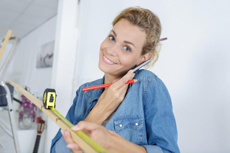 Woman measuring wood with telephone balanced under ear stock photo